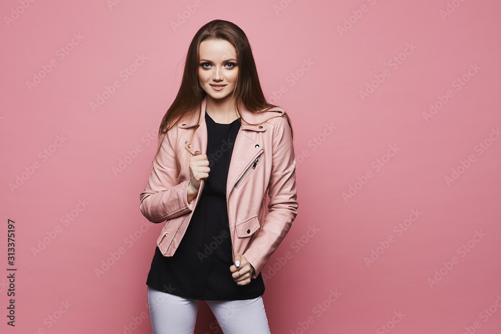 Fototapeta Fashionable young woman in leather jacket posing at the pink background, isolated. Stylish model girl with blond hair in a black blouse and a leather jacket. Beauty in hipster outfit. Young fashion