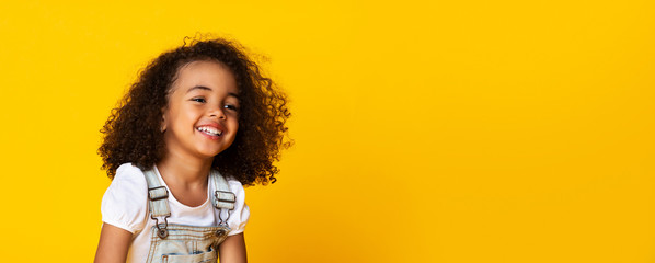 Cute little black girl sincerely laughing over yellow background, long panorama