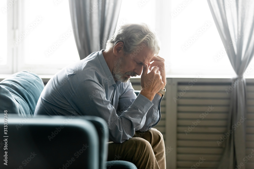 Fototapeta Seated on couch hunched old man looking desperate and lonely