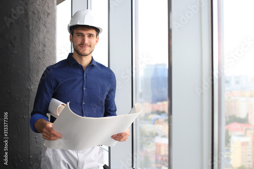 Photo Shot of male architect wearing hardhat and inspecting new building