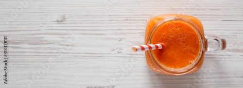Fotomural Homemade Mango Carrot Smoothie in a glass jar mug over white wooden background, top view
