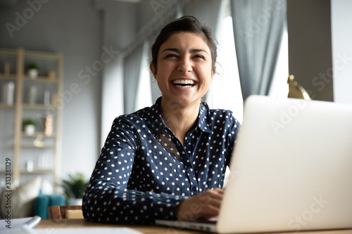 Fototapeta Cheerful indian girl laughing sit with laptop at table obraz