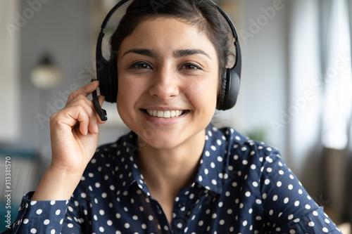 Fototapeta Smiling indian girl professional wear headset look at camera webcam