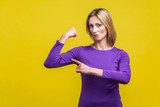I'm strong. Portrait of proud successful businesswoman in elegant purple dress pointing at biceps proud of herself, being independent and confident, feminism. studio shot isolated on yellow background
