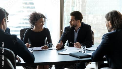 Obraz Multiracial businesspeople brainstorm discuss document at briefing - fototapety do salonu