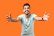 canvas print picture - Come into my arms. Portrait of good natured, extremely happy brunette man with beard in white t-shirt reaching out to camera, stretching arms to hug you. studio shot isolated on orange background