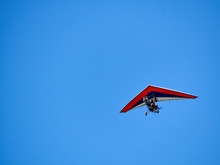 Alone Double Red Wings Paraglider In Blue Sky Background