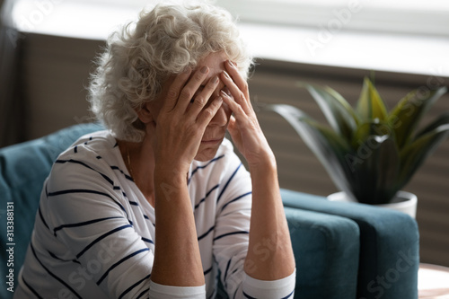 Canvas Print Elderly woman covered face with hands crying feels desperate