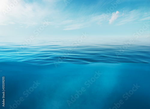 Blue sea or ocean water surface and underwater with sunny and cloudy sky Fototapete
