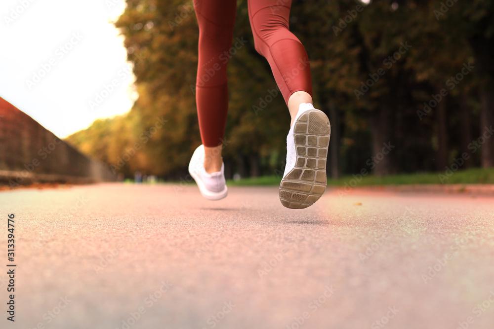 Fototapeta Runner feet running on road closeup on shoe, outdoor at sunset or sunrise.