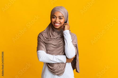 Shy black muslim girl in headscarf posing over yellow background Fototapet