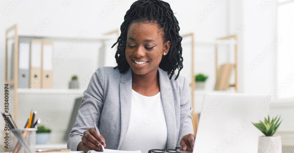 Fototapeta Black Millennial Businesswoman Taking Notes And Working On Laptop In Office