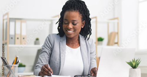 Fototapety, obrazy: Black Millennial Businesswoman Taking Notes And Working On Laptop In Office