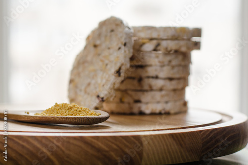 Fotografia, Obraz  Soy lecithin in a wooden spoon on a wooden backgroundand round multigrain rice cakes