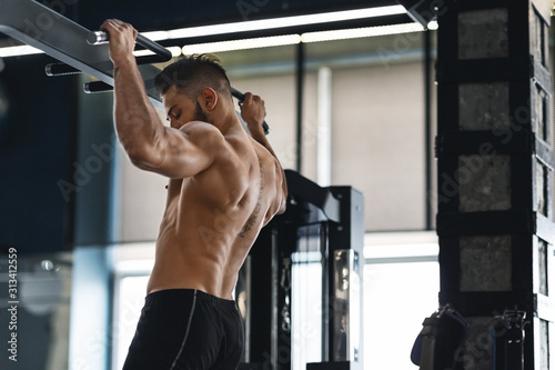 Muscular athlete pulling up on horizontal bar at gym Wallpaper Mural