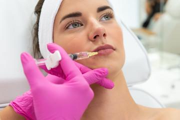 Modelowanie ust kwasem hialuronowym. Twarz kobiety, zabieg powiększania ust. Lekarz medycyny estetycznej wstrzykuje wypełniacz w usta.