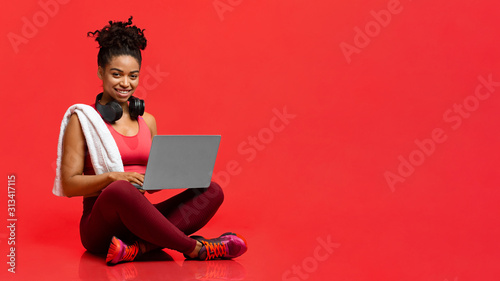 Fotografie, Tablou Smiling sporty athletic woman using laptop over red background