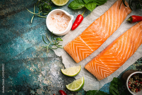 Cuadros en Lienzo  Raw salmon fillet and ingredients for cooking, seasonings and herbs on a blue background