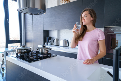 Stampa su Tela Happy attractive joyful brunette female drinking fresh clean filtered purified water at kitchen at home