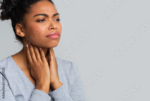 Afro woman suffering from sore throat, touching her neck Canvas Print