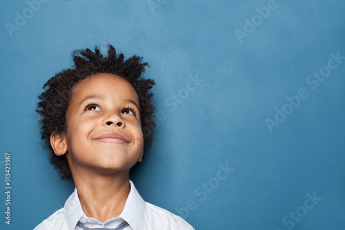Obraz Little black child boy smiling and looking up on blue background - fototapety do salonu