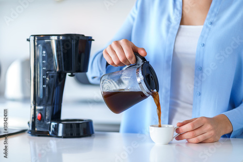 Fotografering Woman using coffee maker for making and brewing coffee at home