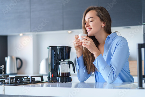 Happy attractive female enjoying of fresh coffee aroma after brewing coffee using coffee maker in the kitchen at home Canvas Print