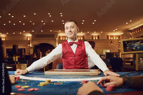 Obraz na plátne Croupier holds poker cards in his hands at a table in a casino.