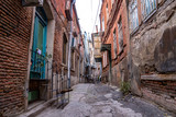 Fototapeta Uliczki - Alley between old houses on an old street in Tbilisi