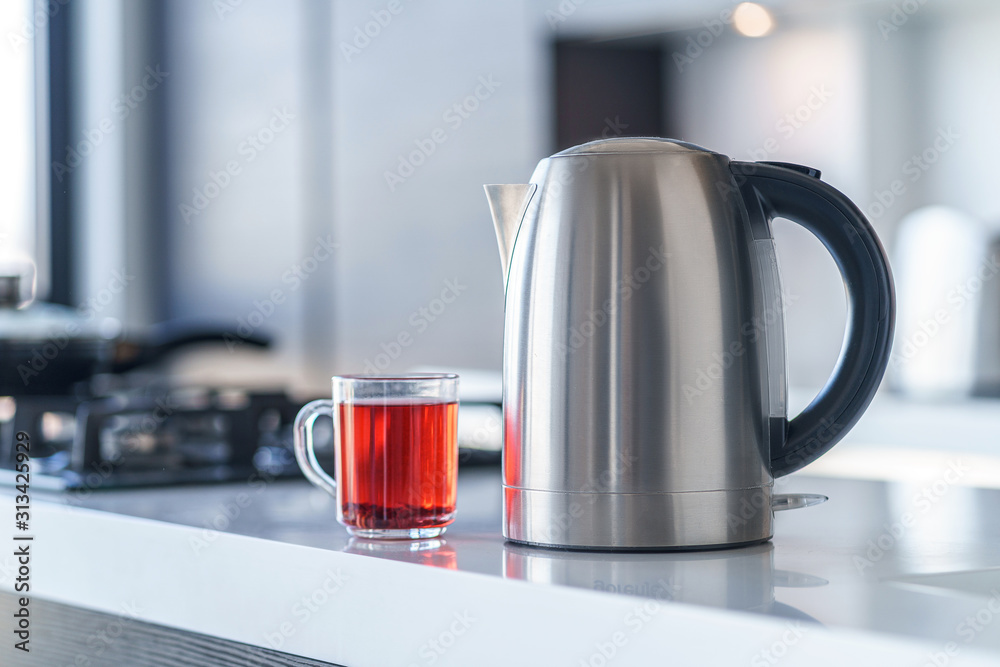 Fototapeta Electric kettle for boiling water and making tea on a table in the kitchen interior. Household kitchen appliances for makes hot drinks