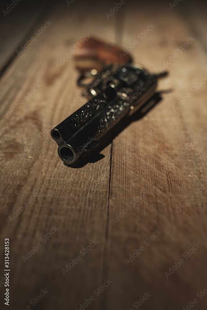 Fototapeta Historic revolver pistol on old wooden floor.