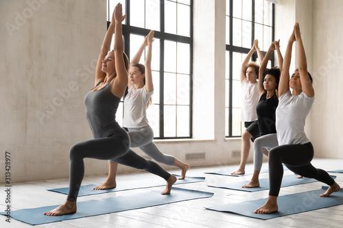 Fotografija Diverse people practicing yoga, standing in Warrior one pose