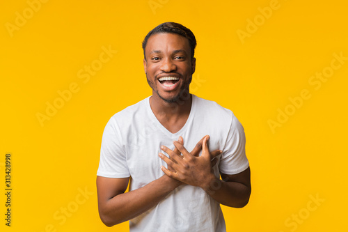 African American Man Laughing Touching Chest Standing Over Yellow Background - 313428998