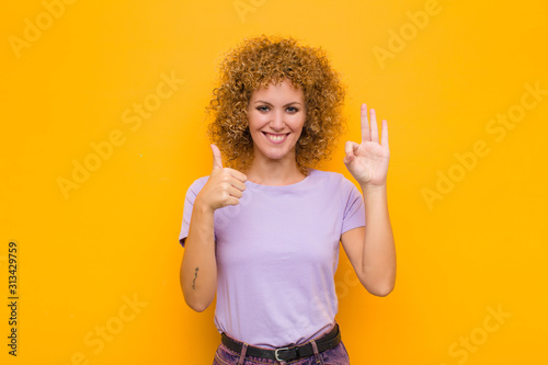 Fototapeta  young afro woman feeling happy, amazed, satisfied and surprised, showing okay an