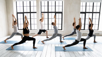 Diverse people standing in Warrior one pose, practicing yoga