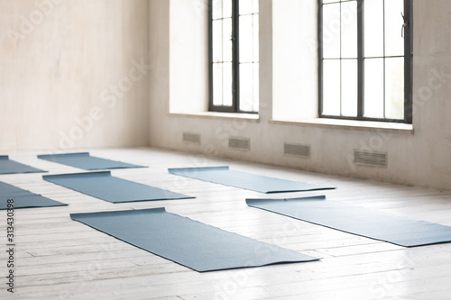 Unrolled yoga mats on wooden floor in empty fitness center - 313430398