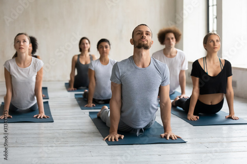 Foto Diverse people doing cobra exercise at group lesson, practicing yoga