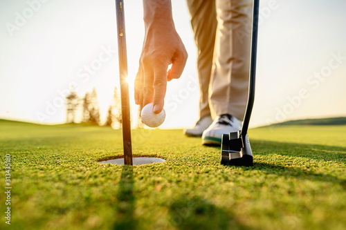 lifestyle, golf, activity, outdoor, sport, golfer concept. Golfers collect golf balls that hole in the green grass on the golf course in the morning.