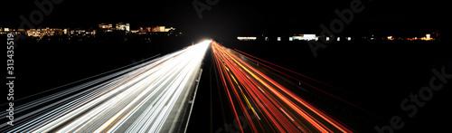 Fotomural  autobahnlichtspuren stadtsilhouette in der nacht