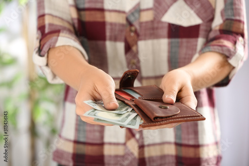 Obraz Woman putting money into wallet on blurred background, closeup - fototapety do salonu