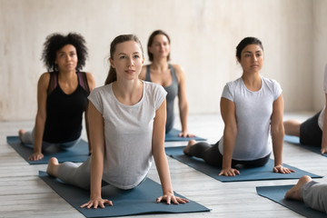 Diverse women doing cobra exercise at group lesson, practicing yoga