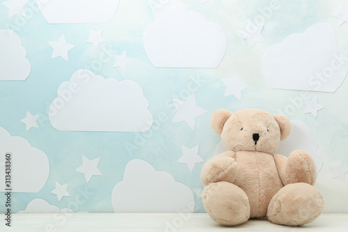 Obraz Teddy bear on white wooden table near wall with blue sky, space for text. Baby room interior - fototapety do salonu