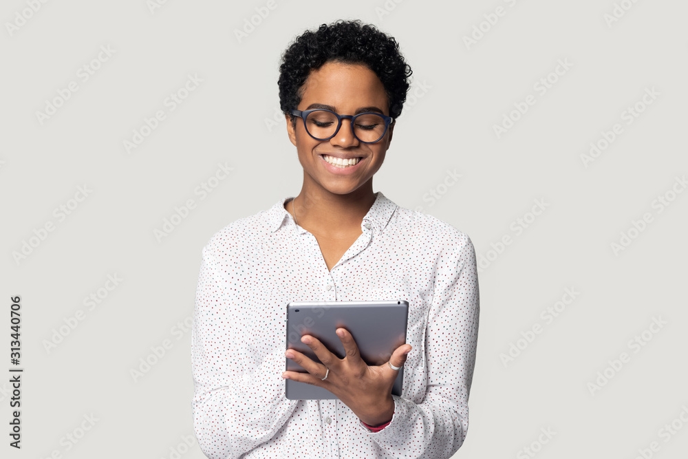 Fototapeta African woman holding tablet do remote online work studio shot