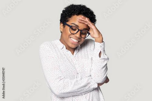 Fototapeta African woman lowers eyes down and looks embarrassed studio shot