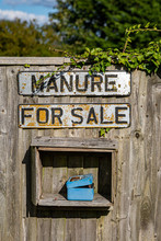 A Manure For Sale Sign On A Wo...