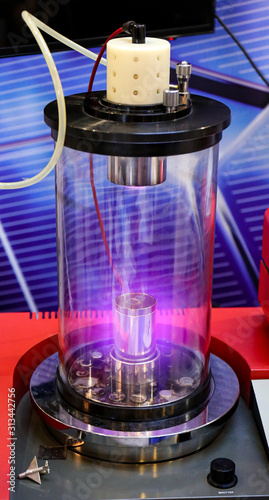 Photo Mangetron sputtering with purple glowing plasma in vacuum glass tube
