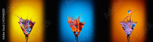 Dice fall in a glasses of martini. Colourful cocktails in glasses with splashes on the dark background. - 313443313