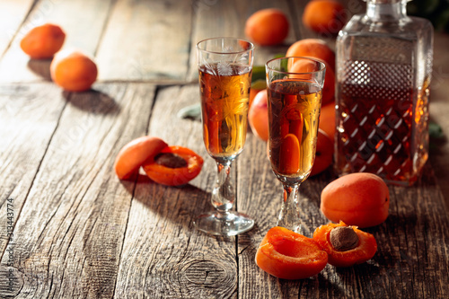 Obraz Apricot liquor and fresh apricots on a old wooden table. - fototapety do salonu