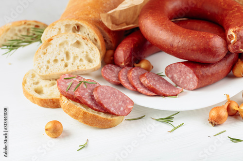 Obraz na plátně  On a white wooden table sausage with bread, rosemary, onion and pepper