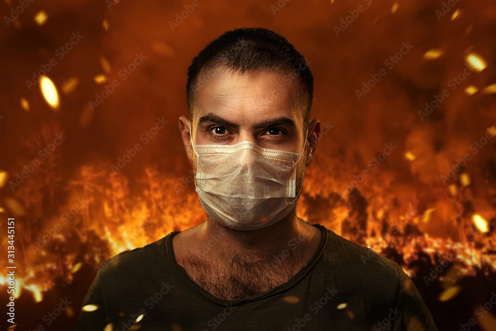 Fototapeta A man in a medical mask to protect the cuts of breath against the backdrop of severe forest fires. The concept of fires in Australia.